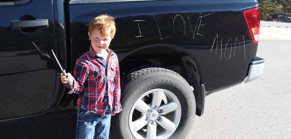 Boy with screwdriver with damaged vehicle