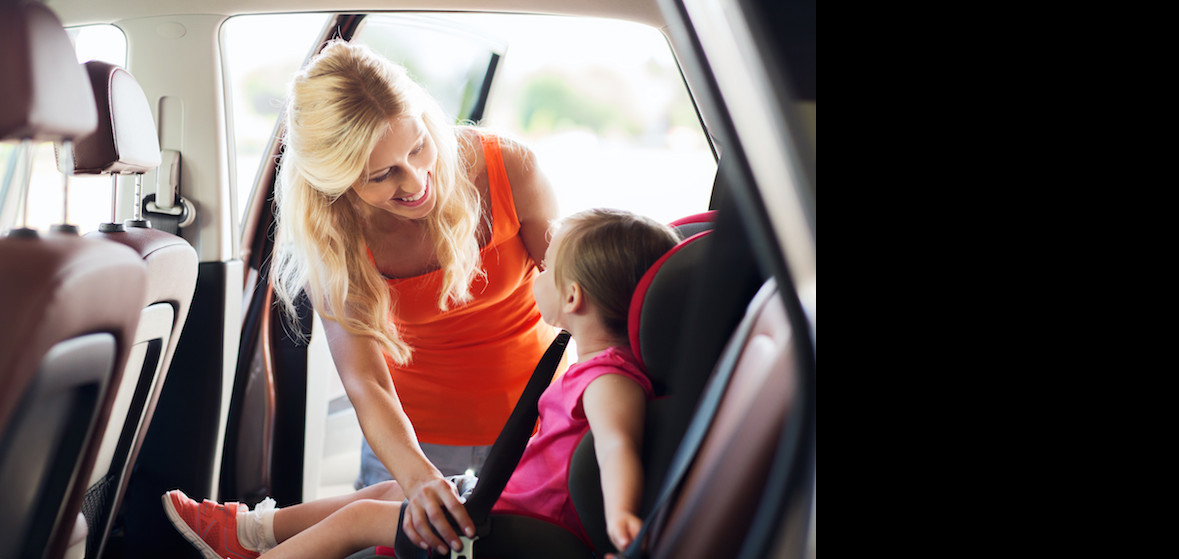 A mom buckling her child into car safely